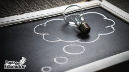 Quadro negro sobre uma mesa com uma lampada tradicional sobre um balão de pensamento desenhado com giz na cor branca.